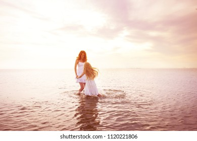 happy weekend by the sea - Mom and daughter in white dresses walking by the sea at sunset. Ukrainian landscape at the Sea of Azov, Ukraine