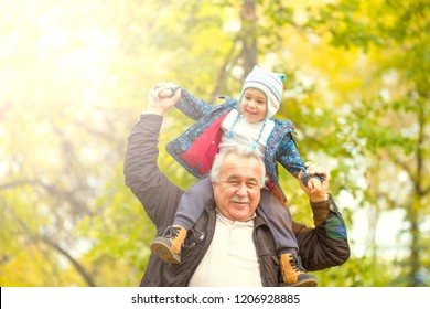 Happy weekend concept. happy grandfather and grandson are walking in the park. Autumn day. Grandpa rolls on the shoulders of a little boy.