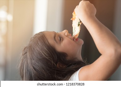 Happy weekend concept little girl at home standing eating slice of pizza smiling joyful close-up blurred background
