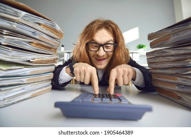 Happy weird man sitting at office desk with stacks of paper files and counting money using calculator. Crazy funny young business accountant managing finances and calculating amount of tax refund