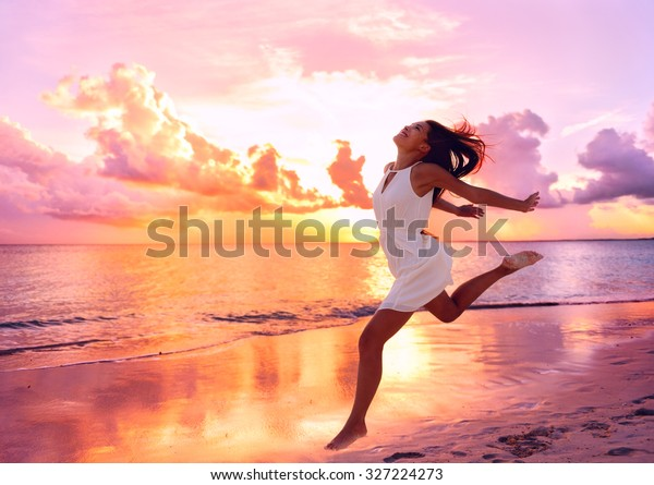 Happy well being free woman jumping of happiness at beach sunset enjoying life in serene picturesque sunset at the ocean . Aspirational happy lifestyle with pretty young Asian lady enjoying freedom.