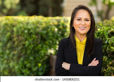 Happy well dressed mature Asian woman smiling.