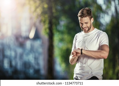 Happy well shaped male standing and looking at smartwatch during training. He is satisfied with results. Copy space in left side