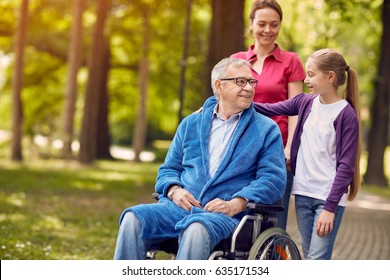 Happy wheelchair man with daughter and granddaughter in park