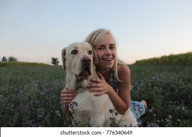 Happy White Blond Girl embracing a White/Cream Labrador Retriever in the middle of a green field.