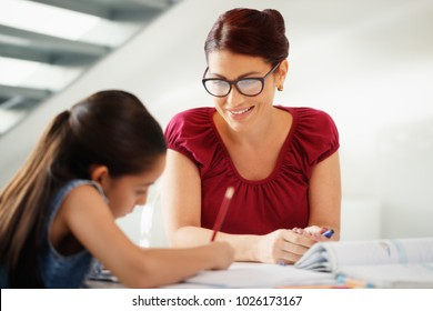 Happy white family at home. Hispanic mother and female child. Latina mom helping daughter with school homework. Education, people, motherhood and relationship, woman teaching and girl learning