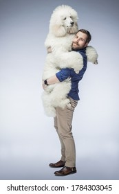 happy white guy holds a white poodle puppy in his arms. A man smiles at his dog in the isolated background. The dog and its owner.
