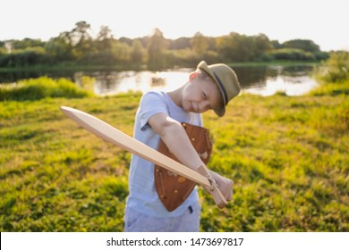 Happy white kid playing outdoor with wooden toys standing in beautiful summer sunset countryside landscape. Boy holding sword and shield in hands happily. Focus at sword. Wide angle photography.