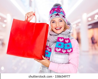 Happy white woman with gifts after shopping to the new year at shop
