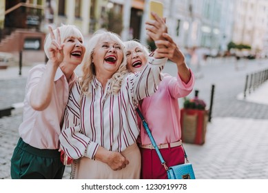 Happy white-haired ladies spending time together while walking through the city