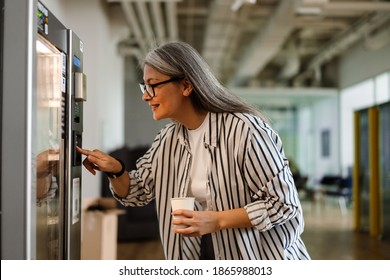 Happy white-haired mature woman using vending machine while drinking coffee indoors