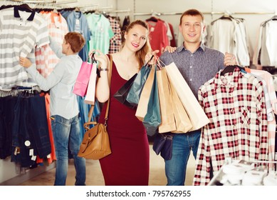 Happy wife and husband with purchases in bags at apparel store