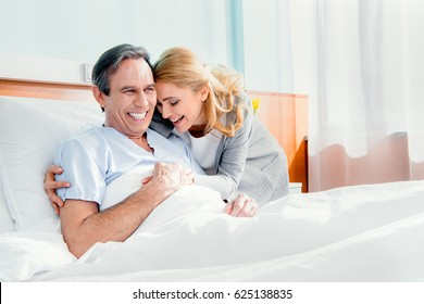 happy wife visiting smiling elderly husband in hospital