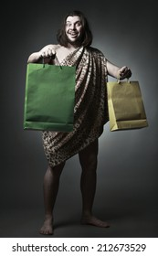 Happy wild man wearing skin of breast hold shopping bags.