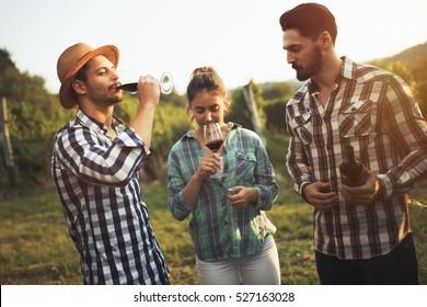 Happy wine tourists tasting wine in vineyard