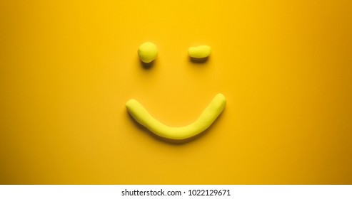 Happy and winking - a yellow emoticon make out of modelling clay on a yellow background.