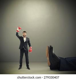 happy winner businessman in red boxing gloves standing near big lying mans legs over dark grey background