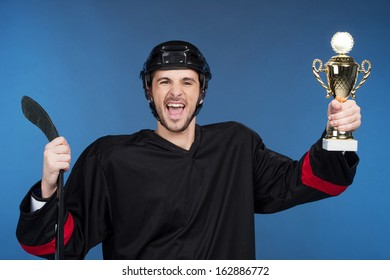 Happy winner holding cup. Celebrating his victory, Isolated on blue