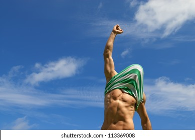 Happy winner with shirt on his head, on blue sky background.