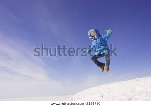 Happy winter day. Flying girl on the blue sky