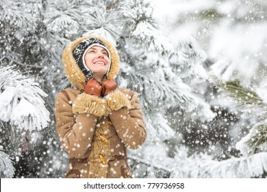 Happy winter fun woman playing throwing snow with arms up open in freedom enjoying the cold season