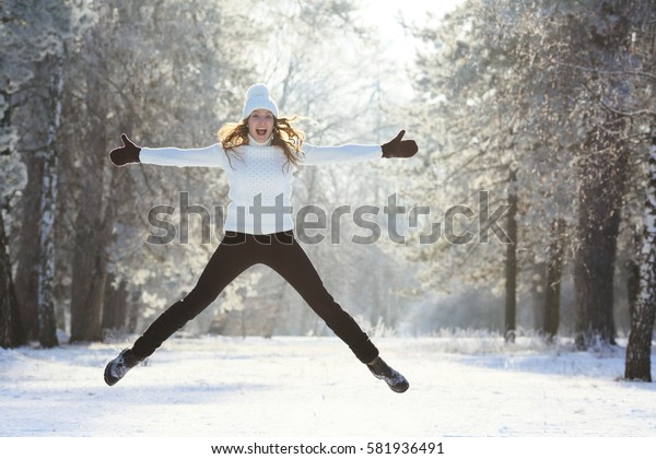 Happy winter girl jumping over the snow in a forest grove