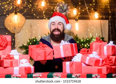 Happy winter holidays. Lot of gifts. Hipster prepared gifts for family. Man santa claus hat celebrate new year. Generous new year. Home is heart of holidays. Wrapped gifts with ribbons and bows.