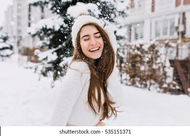 Happy winter moments of joyful young woman with long brunette hair, white winter clothes having fun on street in snowing time. Expressing positivity, true brightful emotions, smiling with closed eyes