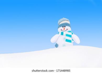 Happy winter snowman against blue sky background