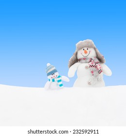 Happy winter snowmen family or friends against blue sky background
