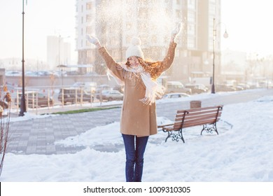 Happy winter time in big city of charming girl walking on street in coat with backpack. Enjoying snowfall, expressing positivity, smiling to camera, joyful cheerful mood, true emotions
