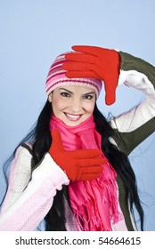 Happy winter woman framing face with hands,she wearing cap,scarf,pullover and gloves over blue background