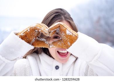 Happy winter woman show snow heard. Outdoor beautiful girl. Winter holidays. Snowfall