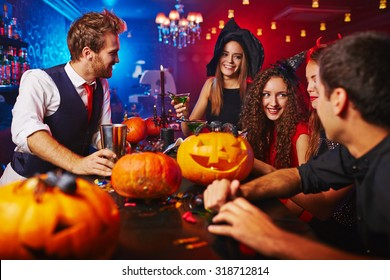 Happy witches celebrating Halloween in bar