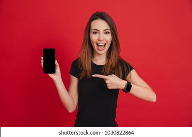 Happy woman 20s with long brown hair smiling and gesturing finger aside on black screen of cell phone isolated over red background