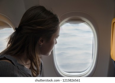 Happy woman admiring the view from the window of the plane