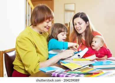 Happy woman with adult daughter and two children playing at home interior. Focus on mature