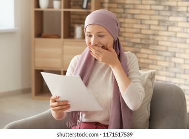 Happy woman after chemotherapy reading test results at home