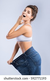 Happy woman after weight-loss is try her old jeans