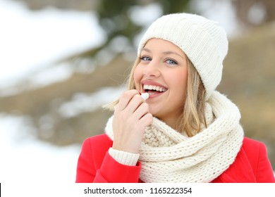 Happy woman applying lip balm outdoors in winter in the snowy mountain