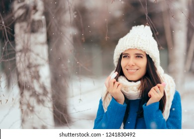 Happy Woman Applying Lip Balm Outdoors in Winter. Girl with dry chapped lips using moisturizer lipstick