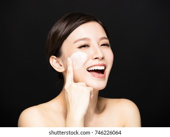 happy woman applying lotion cream on face