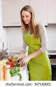 Happy  woman  in apron slicing vegetables in home