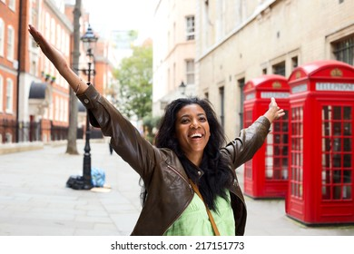Happy woman with arms outstretched in London
