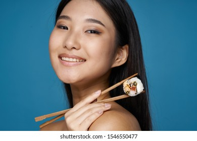 A happy woman with an Asian appearance holds in her hand two chopsticks and traditional Japanese food