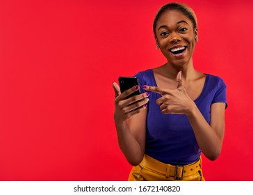Happy woman in aT-shirt with ear rings with a phone.