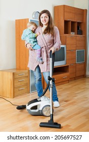 Happy woman with baby cleaning living room with vacuum cleaner