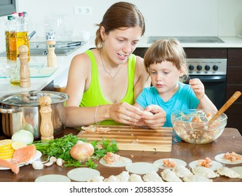 Happy woman with baby cooking fish dumplings (pelmeni) together