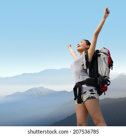 happy woman with backpack raised arm hands and looking to sky on the top of mountains. asian