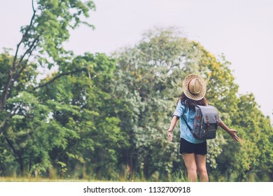 Happy woman backpacker looking at the view with arms outstretched in forest, freedom and active lifestyle concept